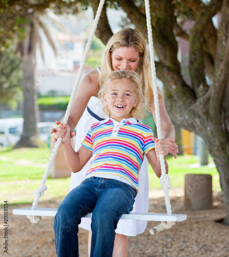 Jolly mother pushing her daughter on a swing