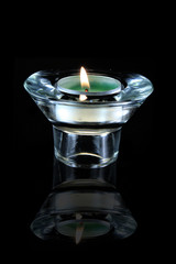green candle in glass holder with flame and reflection