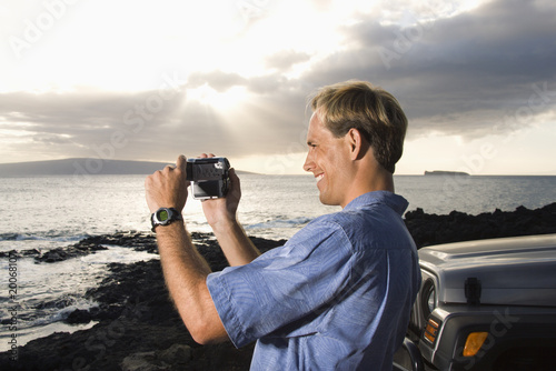Man Using Video Camera at the Beach