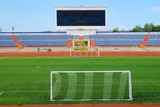 STADIUM - Football field with goal and tablo on blue sky poster
