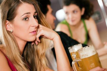 Leute in einer Bar, Frau ist traurig und verlassen