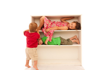 Three young kids playing on bookshelf