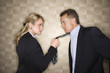 Angry Businesswoman Pulling Man's Tie