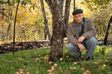 Thoughtful middleaged man sit under apple-tree