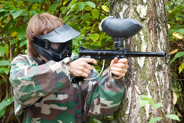 paintball player is shooting aside in the forest