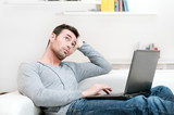 Pensive casual man working on laptop