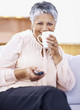 Elderly woman holding TV remote while drinking coffee