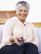 Happy old woman with a television remote control