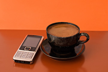 cup of coffee and mobile phone on brown and orange background