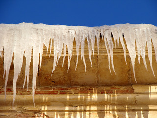 icicles hanging from old building roof