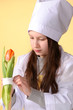 Preteen girl in nurse uniform taking care on flower