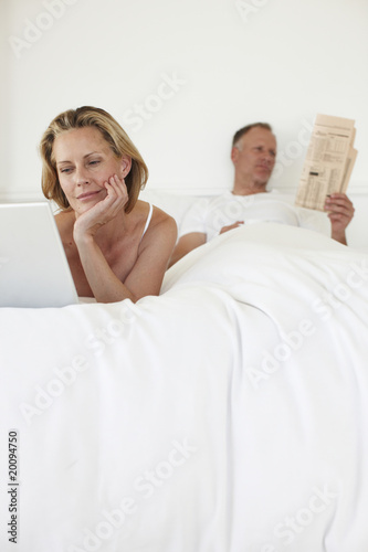 Couple relaxing in their bed