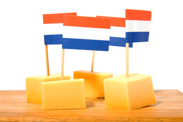 cheese cubes on wooden board over white background
