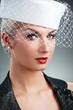 Beautiful young woman in white hat with net veil.