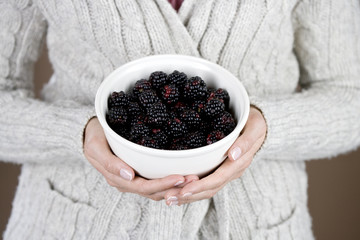 A woman holding a bowl of blackberries