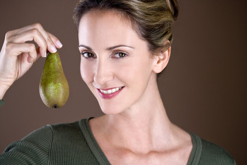 A mid adult woman holding a pear