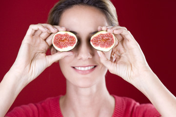 A mid adult woman holding figs up to her eyes