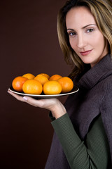A mid adult woman holding a plate of clementines