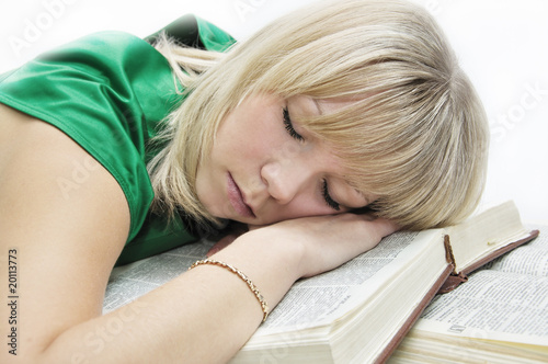 The girl was tired and sleeping on the books