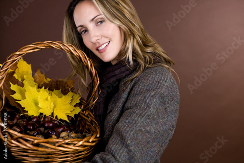 A woman holding a basket of conkers, acorns and autumn leaves
