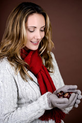A mid adult woman holding a handful of conkers