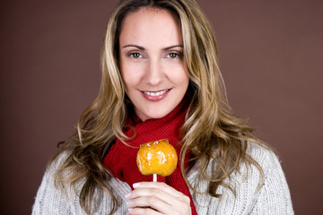 A mid adult woman holding a toffee apple, smiling