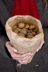 A woman holding a bag full of mixed nuts