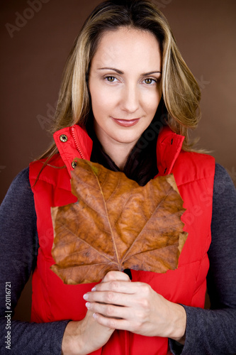 A mid adult woman holding a dried leaf