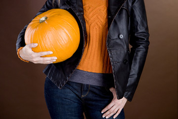 A mid adult woman holding a pumpkin