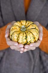 A woman holding a small pumpkin, close-up