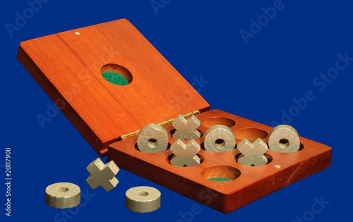 tic tac toe game in old natural wood box isolated on blue