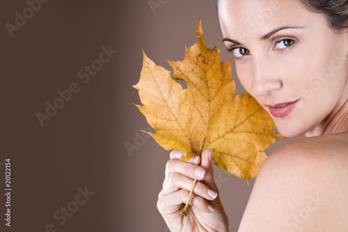 Portrait of a mid adult woman holding a dried leaf