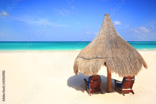 Grass hut and chairs on a gorgeous beach resort