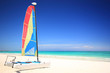 A colorful catamaran sailboat on a gorgeous tropical beach