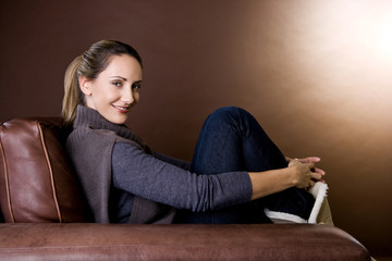 A mid adult woman relaxing in an armchair