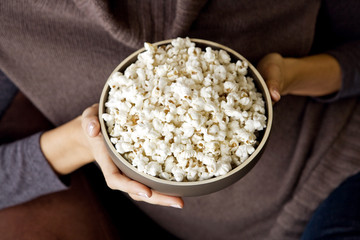 A woman holding a bowl of popcorn