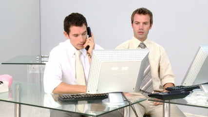 Low-spirited businessmen talking on phone in the office
