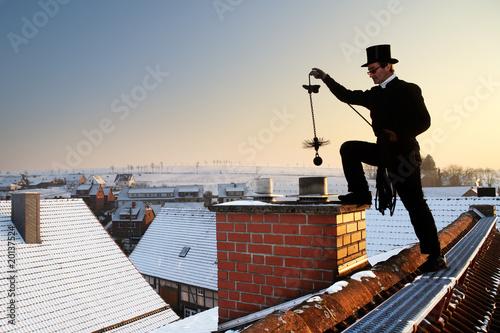 Leinwandbild Motiv chimney sweep with stovepipe hat upon the roof