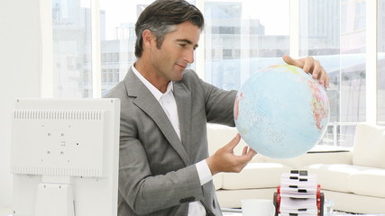 Ambitious businessman holding a terrestrial globe