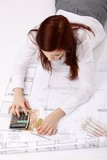 lying woman with construction plan, calculator, money, coins