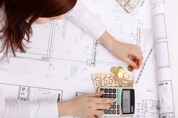hands with house construction plan, calculator, money, coins