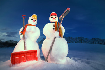 snowwoman and snowman with snow shovel and broom by night