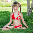 Little girl sit in lotus position and meditate. Yoga summer.