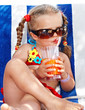 Child girl in sunglasses and red bikini drink  juice. Summer.