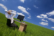 Man Relaxing At Office Desk & Computer In a Green Field