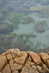 Rock ledge overlooking calm, clear, seawater