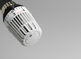 heater thermostat in front of unsharp light grey fond