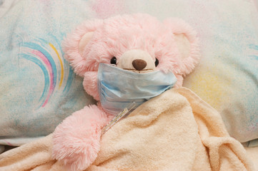 pink bear is ill in a bed