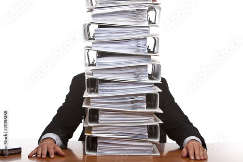 Frustrated Business man in office with huge paperwork (folders)