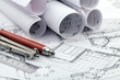 rolls of architectural blueprints, ruler, pencil, compass